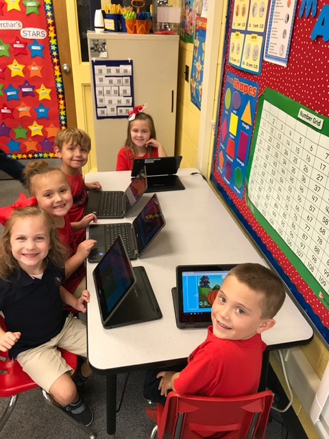 Kindergarten students work with touch screen chrome books!